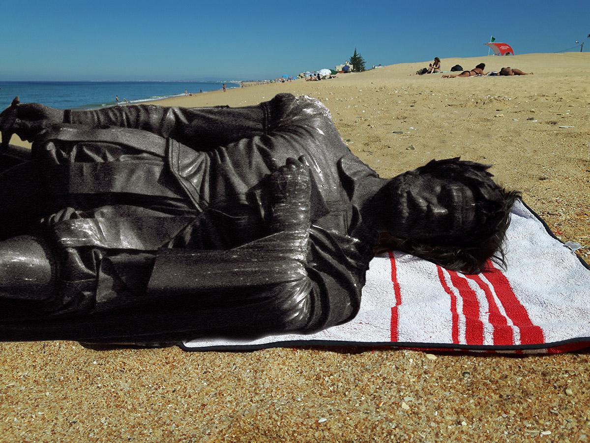 Camões deitado em cima de uma toalha na praia, ao sol.