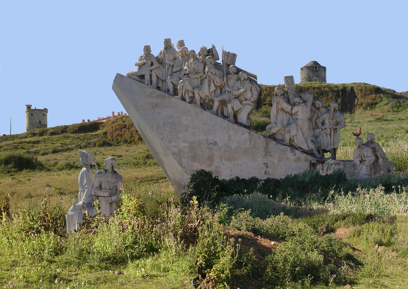 Esculturas do Monumento aos Descobrimentos no campo. Moínhos em ruínas ao fundo.