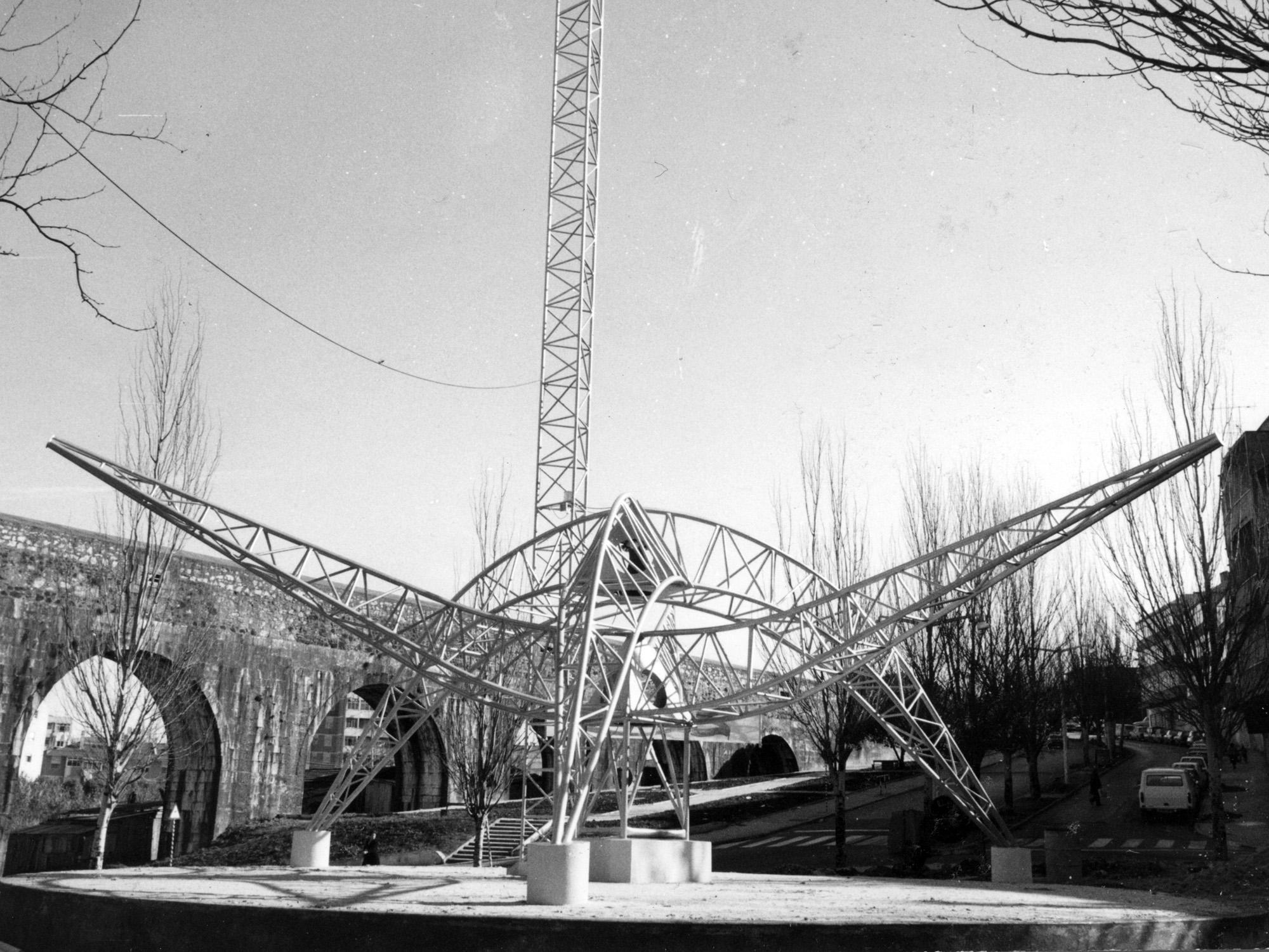 O monumento na Praça das Águas Livres com os arcos do aqueduto ao fundo.