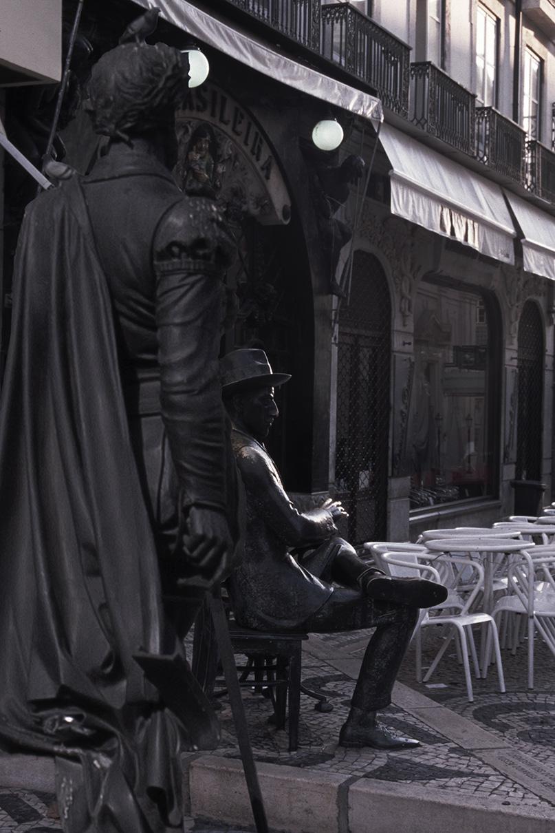 Camões de pé, atrás de Fernando Pessoa.