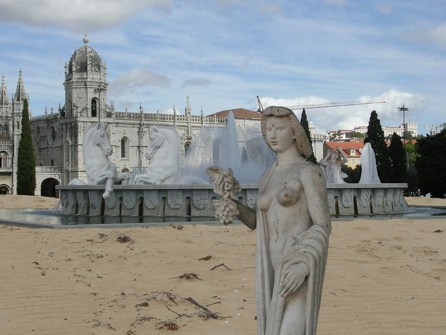Fonte da Praça do Império rodeada de areia; as esculturas dos cavalos marinhos tomam banho na fonte e uma escultura de mulher anda sobre a areia.
